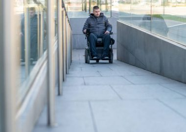 Man in a wheelchair using a ramp next to stairs